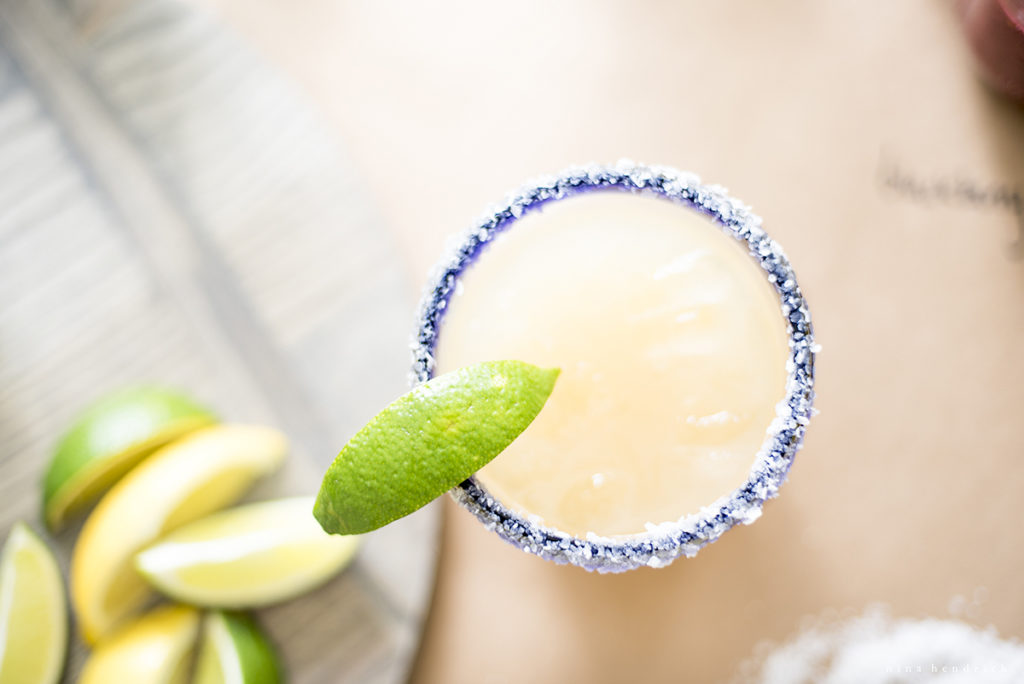 overhead of classic margarita with salt rim and limes