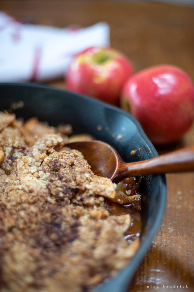 lodge pan with new england apple crisp and a wooden spoon