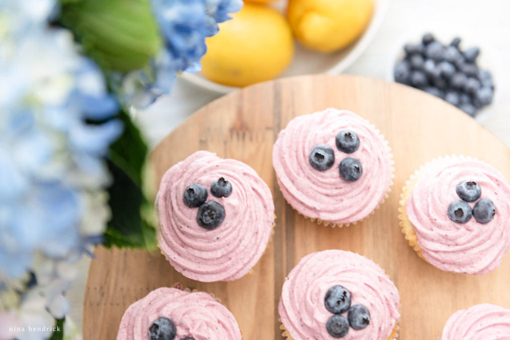 Overhead shot of lemon blueberry cupcakes on wooden plate.