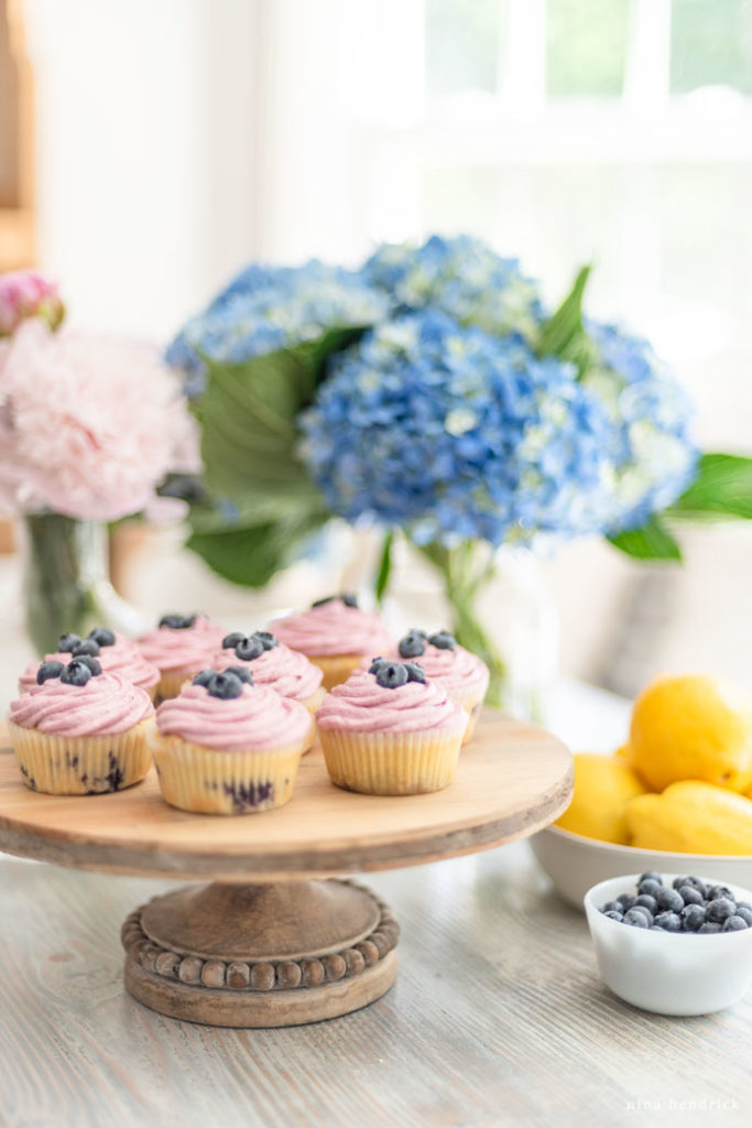 Cupcakes on wooden cake stand with flowers.