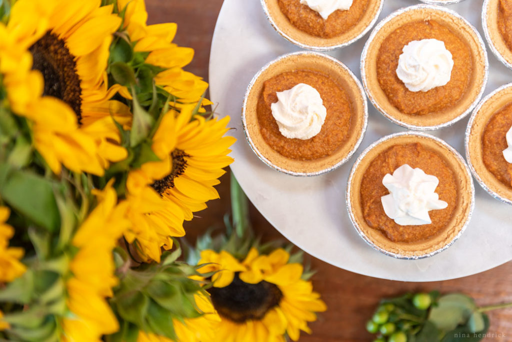 mini no-bake pumpkin pies on marble cake stand with sunflowers