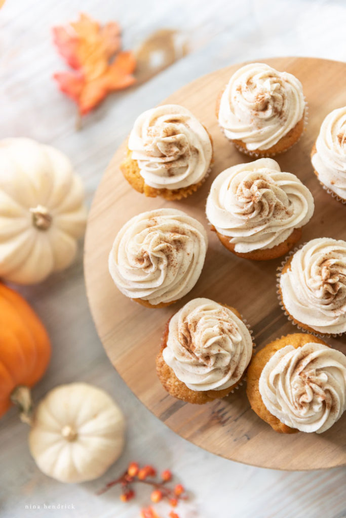 overhead view of pumpkin spice cupcakes with cinnamon cream cheese frosting and cinnamon sprinkle garnish