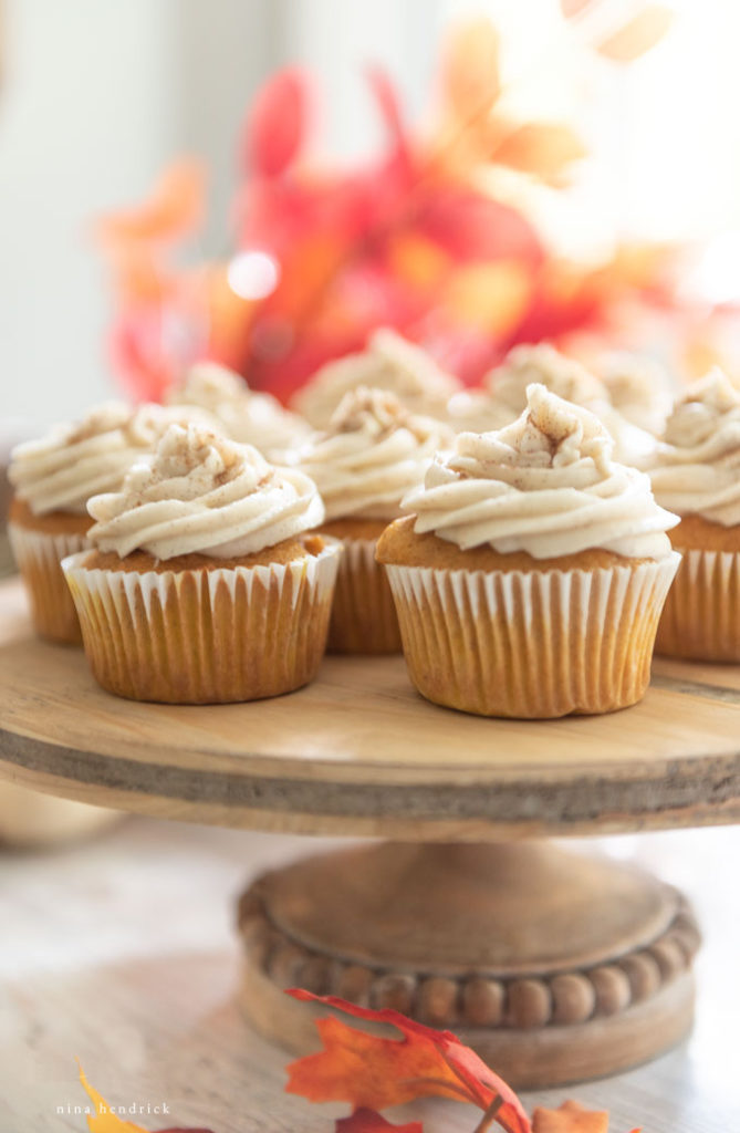 pumpkin spice cupcakes on a wooden cake stand