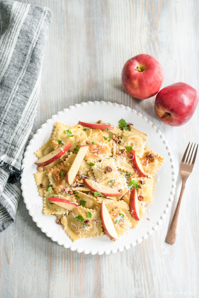Ravioli on a white plate with gold fork and apples