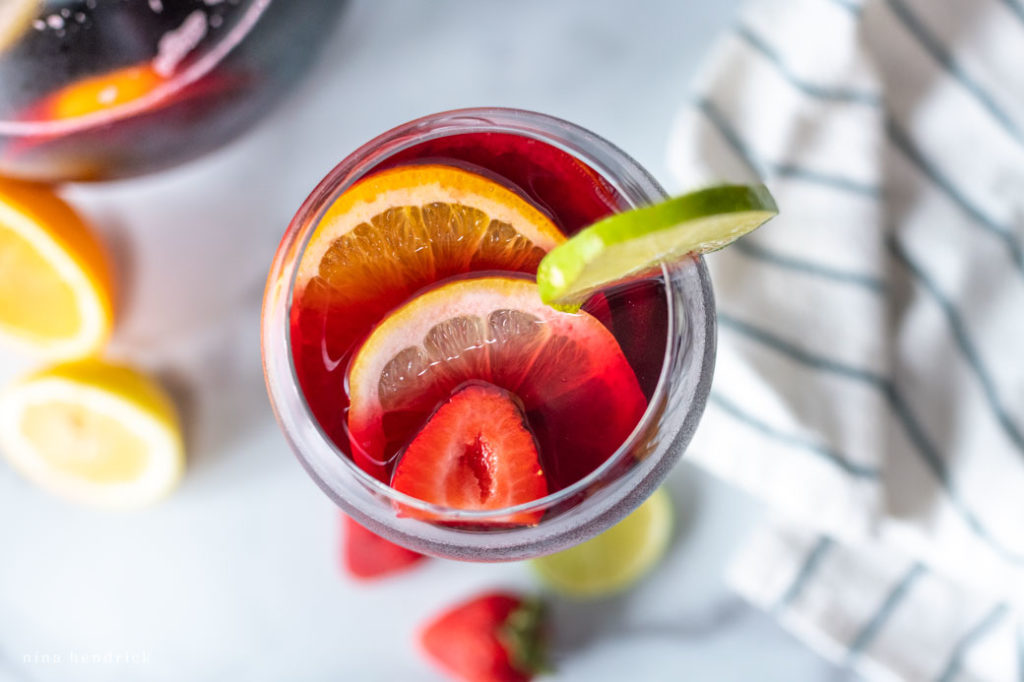 overhead view of sangria cocktail with citrus and strawberries